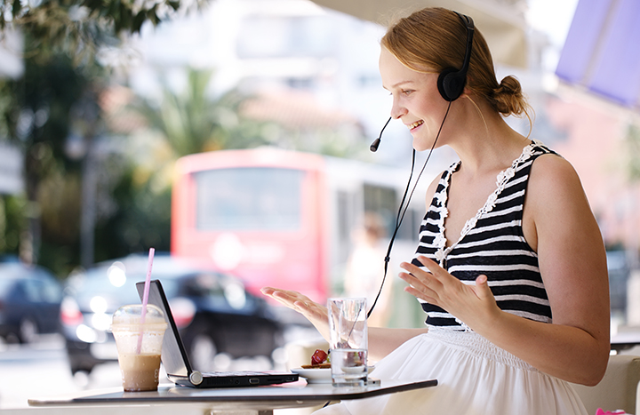 Laughing attractive blond woman wearing a headset sitting with a laptop at an open-air restaurant enjoying refreshments and talking to her friend using skype